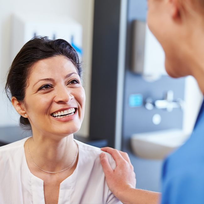 Woman smiling at dentist during preventive dentistry appointment