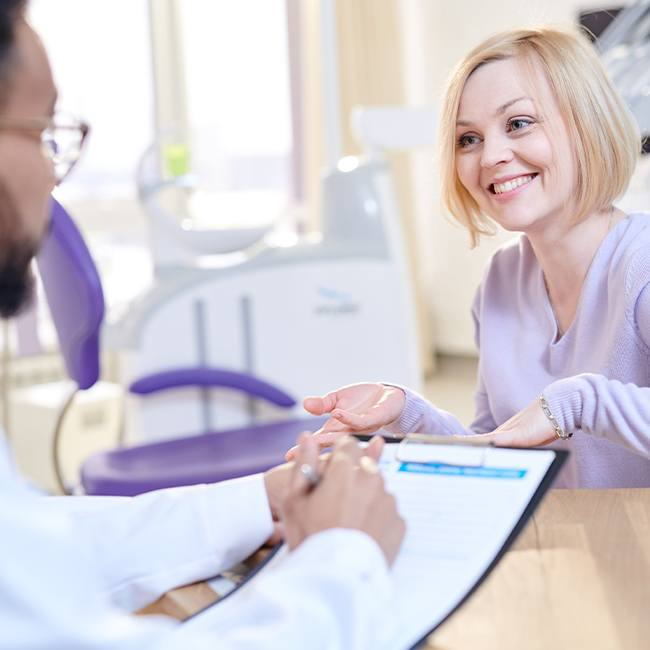 Woman talking to dentist about dental insurance forms